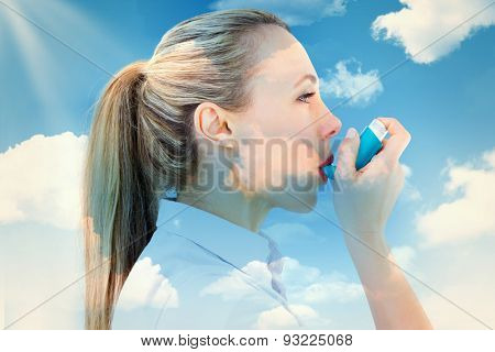 Pretty blonde using an asthma inhaler against blue sky