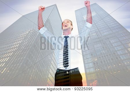 Handsome businessman cheering with arms up against low angle view of skyscrapers