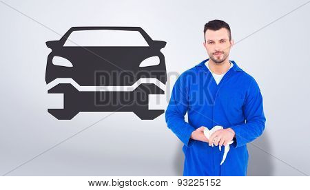 Mechanic wiping hands with cloth against grey vignette