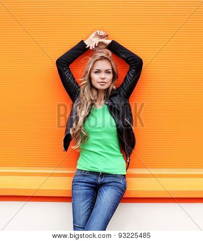Fashion Portrait Of Beautiful Blonde Woman Wearing A Black Rock Leather Jacket Against The Colorful