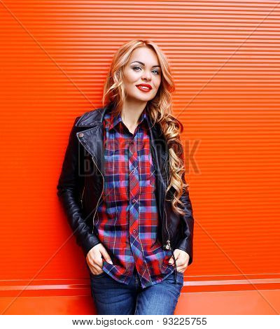 Portrait Of Pretty Blonde Woman Wearing A Black Rock Leather Jacket Against The Colorful Red Wall, S