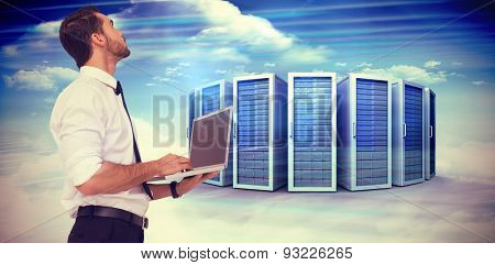 Sophisticated businessman standing using a laptop against composite image of server towers