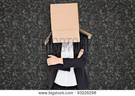 Businesswoman lifting box off head against black background