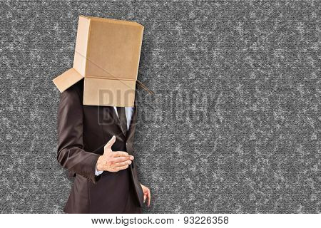 Anonymous businessman offering his hand against grey background