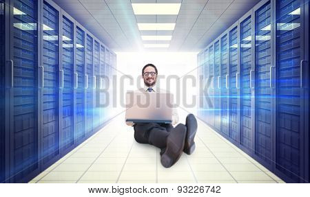 Businessman using laptop against digitally generated server room with towers