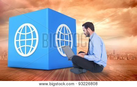 Businessman sitting on the floor using his laptop against sun shining over city