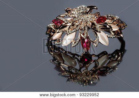 golden bracelet with precious stones on grey background