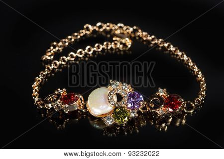 golden bracelet with precious stones on black background