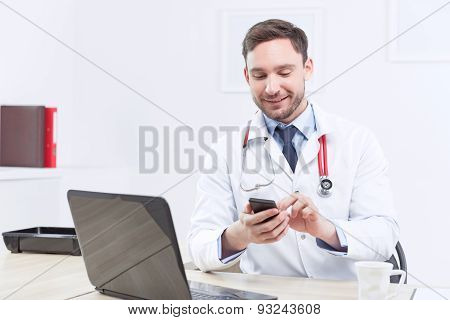 Smiling cardiologist holding the mobile phone