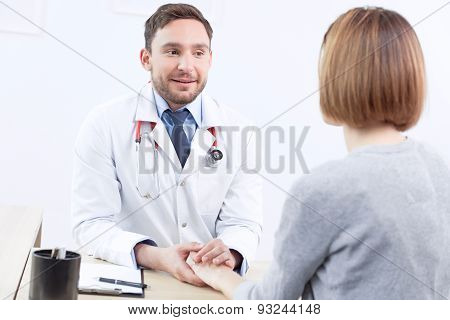 Nice doctor holding the hand of  patient