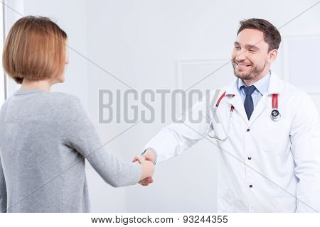 Nice doctor shaking hands with the patient