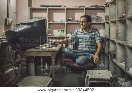 JODHPUR, INDIA - 16 FEBRUARY 2015: Indian man sits in office cross-legged on chair in front of computer screen. Post-processed with grain and texture.