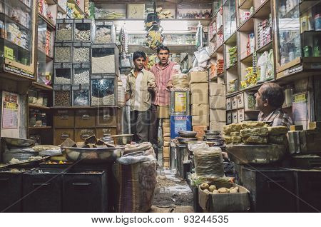 JODHPUR, INDIA - 10 FEBRUARY 2015: Three men in various merchandise store talk business. Post-processed with grain and texture.