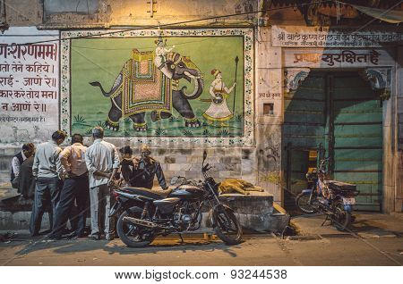 JODHPUR, INDIA - 16 FEBRUARY 2015: Elderly Indian men play cards on street while dog sleeps and motorbikes parked by. Post-processed with grain and texture.