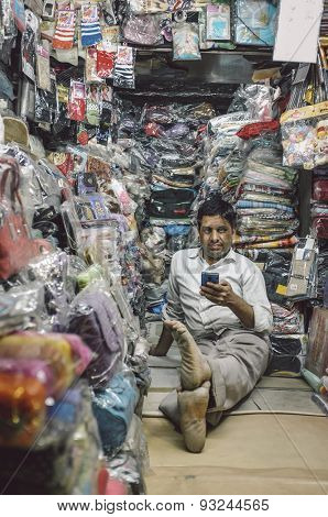 JODHPUR, INDIA - 07 FEBRUARY 2015: Store owner sits on floor of little textile shop overflown with different merchandise and waits for customers. Post-processed with added grain and texture.