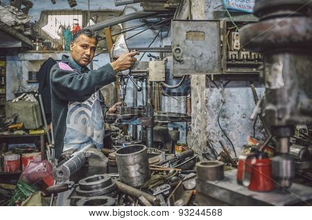 JODHPUR, INDIA - 07 FEBRUARY 2015: Indian mechanic works in workshop filled with scattered tools and machines. Post-processed with added grain and texture.