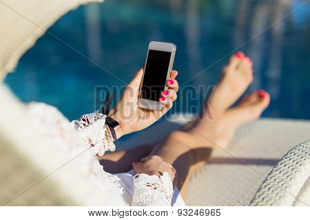 Woman sitting in deck chair by the swimming pool and using mobile phone
