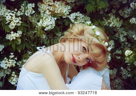Beautiful Blonde Woman In White Sundress Sitting On The Grass Near White Flowers