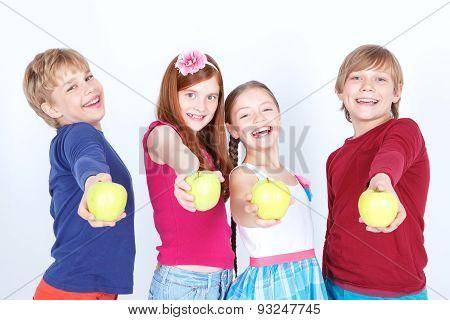 Positive friends keeping apples.