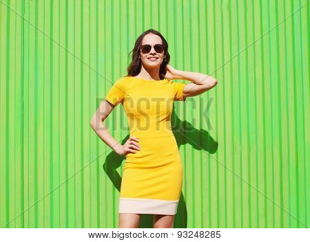 Fashion Summer Portrait Of Beautiful Young Woman In Yellow Dress And Sunglasses Against The Colorful