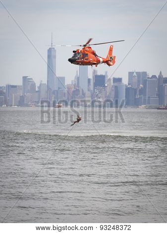 STATEN ISLAND, NY - MAY 24 2015: A Coast Guard rescue swimmer is hoisted line into a US Coast Guard MH-65 Dolphin helicopter for a Search and Rescue demonstration at Sullivans Pier during Fleet Week.