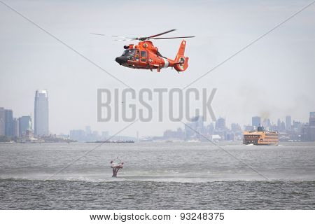 STATEN ISLAND, NY - MAY 24 2015: A Coast Guard rescue swimmer grabs the rescue basket lowered by a USCG MH-65 Dolphin helicopter amidst a downdraft at a Search and Rescue demonstration for Fleet Week.
