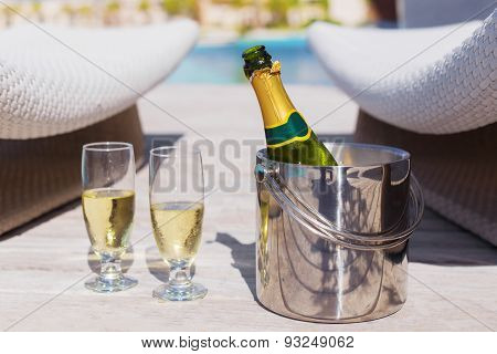 Champagne bottle in bucket and two glasses of champagne