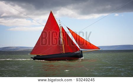Traditional wooden boat Galway Hooker with red sail compete in regatta. Ireland.