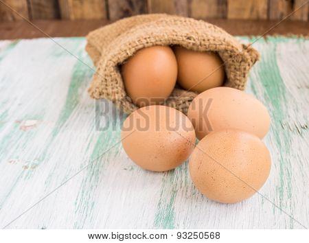 Egg In Burlap Sack On Wooden Background