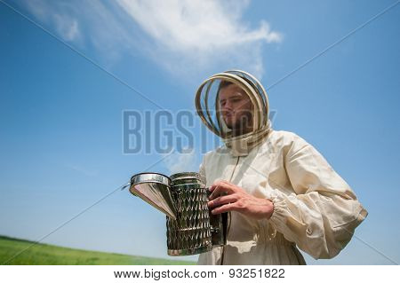beekeeper with smoke tool. making clouds