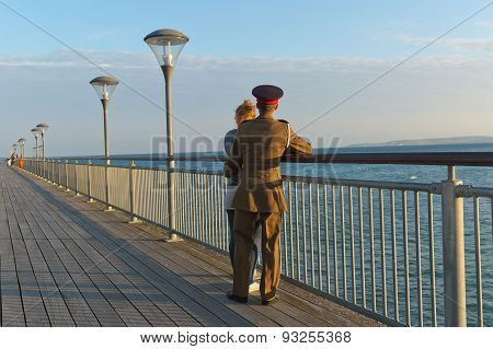 A Girl In A Track Suit And A Guy In His Army Suit Turning Away From The Camera, Looking At The Sea,