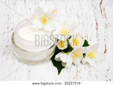Face And Body Cream Moisturizers With Jasmine Flowers On White Wooden Background