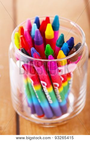 Colorful pastel crayons in glass holder, closeup