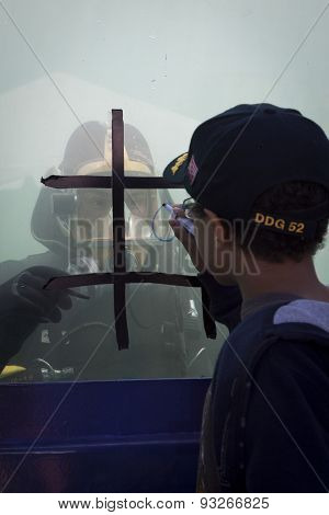 STATEN ISLAND, NY - MAY 24 2015: An unidentified boy plays tic tac toe against a U.S. Navy EOD technician through the glass of a 6,800 gallon mobile dive tank on Sullivans Pier at Fleet Week NY 2015.