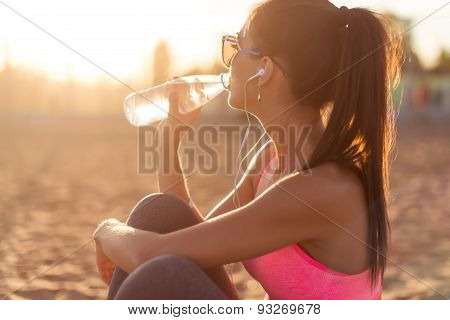 Beautiful fitness athlete woman drinking water after work out exercising on sunset evening summer in
