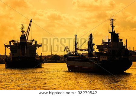 Commercial cargo ships at sunset sailing on a bay
