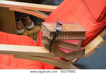 Stack Of Books With Glasses On Chair