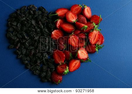 Strawberry and prunes in shape of heart on blue background
