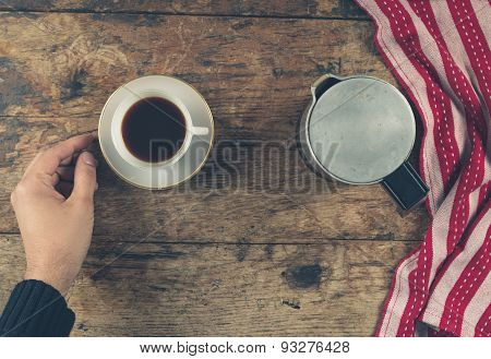 Hand With Cup Of Coffee On Wood