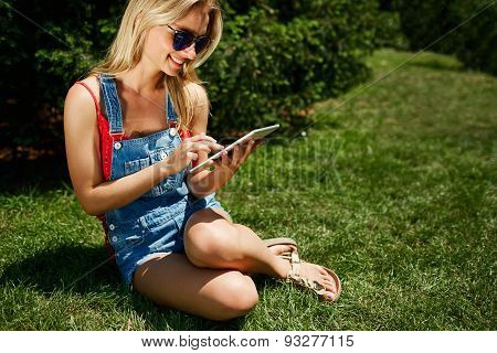 Portrait Of Happy Young Blonde Woman College Student Use Tablet Pc Sitting On Grass In Park.