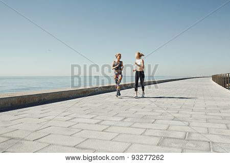 Couple Female Running Exercising Jogging Happy On Waterfront Training As Part Of Healthy Lifestyle.