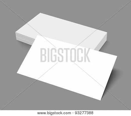 Stack of blank business card on gray background with shadows.