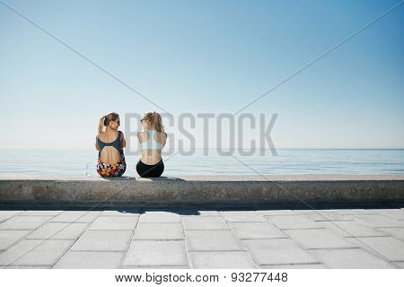 Sport Fitness Girls Relaxing After Training Outdoor. Young Couple Talking Sitting In Waterfront Afte