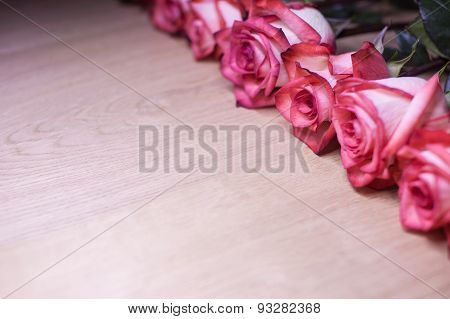 Several pink roses on a wooden background