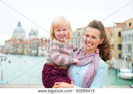 Smiling Mother Holding Happy Daughter In Venice On Bridge