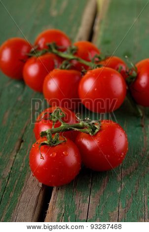 Juicy Cherry Tomatoes On Green Table