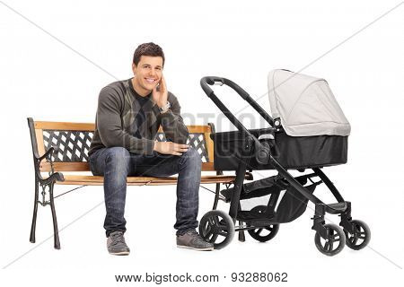 Young father sitting on a wooden bench with a baby stroller beside him isolated on white background