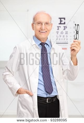 Vertical shot of a mature optician holding a pair of glasses and posing in his office in front of an eye chart