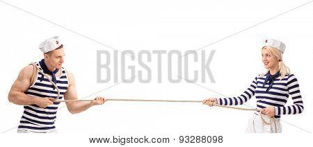 Studio shot of a male and a female sailor playing tug-of-war isolated on white background