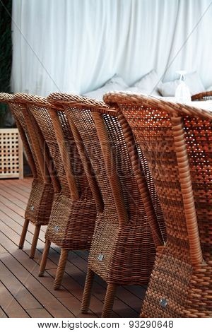 Four brown woden rattan armchairs